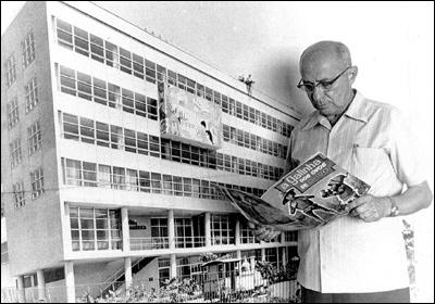 Adolfo Aizen, na década de 70, em frente a uma foto ampliada da Ebal, quando já se dedicava mais aos livros infantis. Note o sugestivo nome do exemplar nas mãos do editor. Cortesia da família Aizen.
